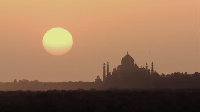 WS Silhouette of Taj Mahal against orange sky at sunrise / Agra, Uttar Pradesh, India