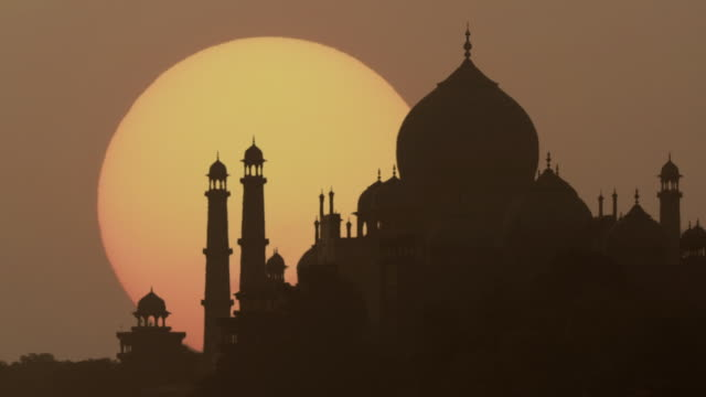 vidéos et rushes de high speed ms silhouette of taj mahal at sunrise / agra, uttar pradesh, india - inde