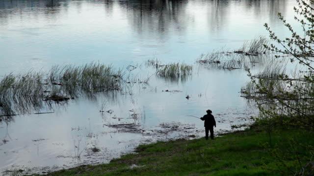 vídeos de stock, filmes e b-roll de silhueta do pescador pescar no rio - lago reflection