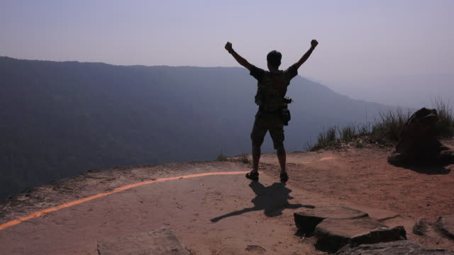 Silhouette of the man Hiking the mountain man on the mountain top outstretched