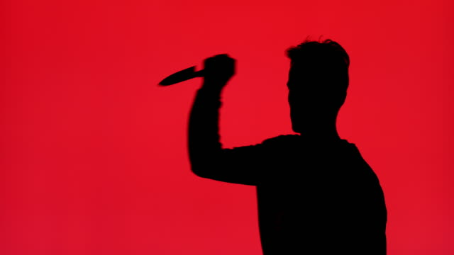 silhouette of the man lifts his hand to stab with knife - knife crime stock videos & royalty-free footage