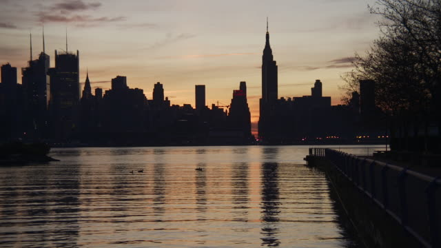 silhouette of the new york city skyline from new jersey showing the hudson river, the empire state building, the new yorker, and the chrysler building at sunrise - establishing shot点の映像素材/bロール