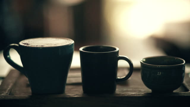 vídeos de stock e filmes b-roll de silhouette of three different coffee cups on wooden tray with blurred backgrounds. - chávena