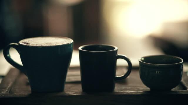 vídeos y material grabado en eventos de stock de silueta de tres tazas de café diferentes en bandeja de madera con fondos borrosos. - cup