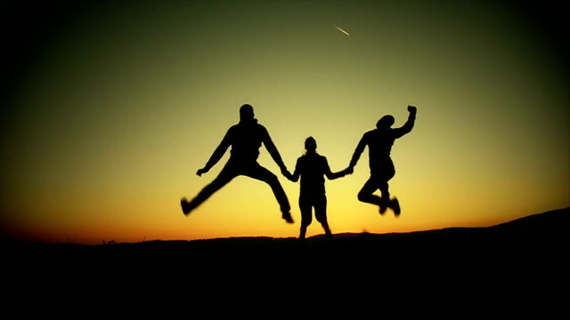 Silhouette of three friends jumping