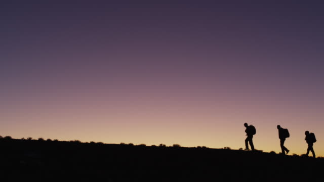 WS Silhouette of three people hiking in desert at sunset / Moab, Utah, USA