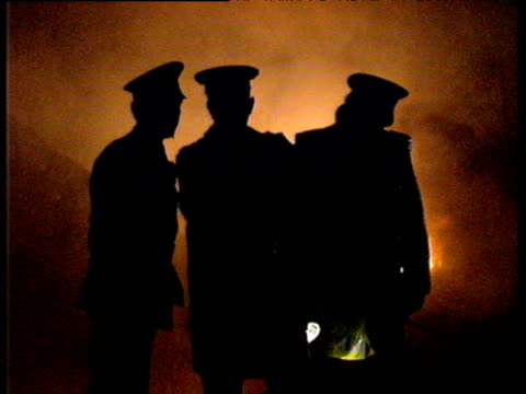 silhouette of three policemen against flames lockerbie air disaster 21 dec 88 - lockerbie stock videos & royalty-free footage