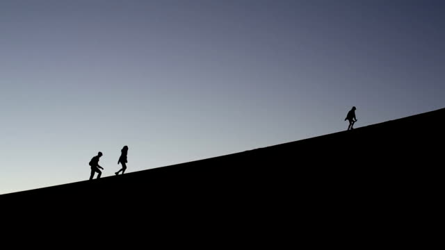 stockvideo's en b-roll-footage met silhouette of tourists climbing the famous dune 45 at sunrise - namibië
