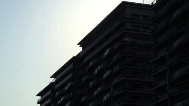 silhouette of tower apartment with sun - town stock videos & royalty-free footage