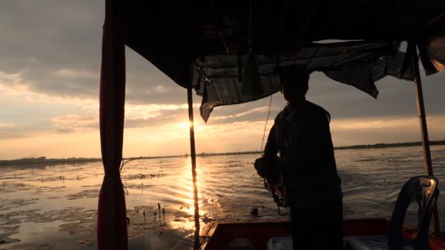 湖の伝統的な漁師のシルエット - 男漁師点の映像素材/bロール