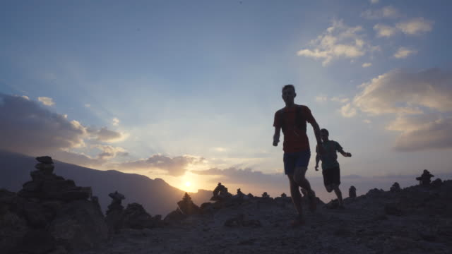 Silhouette of trail runners passing by at sunrise
