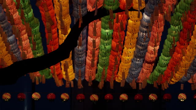 cu la silhouette of tree branch with rows if colorful paper lanterns in background at jogyesa temple, buddha's birthday, seoul, south korea - buddha's birthday stock videos and b-roll footage