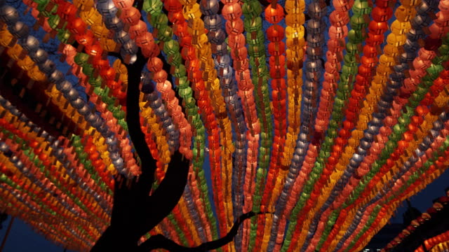 cu la silhouette of tree trunk with rows if colorful paper lanterns in background at jogyesa temple, buddha's birthday, seoul, south korea - buddha's birthday stock videos and b-roll footage