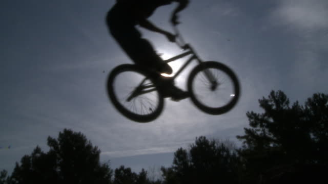 SLO MO WS Silhouette of two BMX bikers jumping, sun shining in background / Jacksonville, Florida, USA