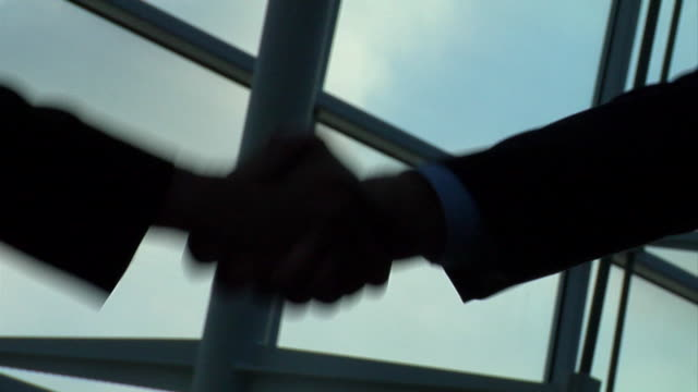 cu silhouette of two businessmen shaking hands in glassy modern building/ virginia beach, virginia - 合意点の映像素材/bロール