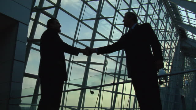 ms silhouette of two businessmen shaking hands in modern building/ virginia beach, virginia - suit stock-videos und b-roll-filmmaterial