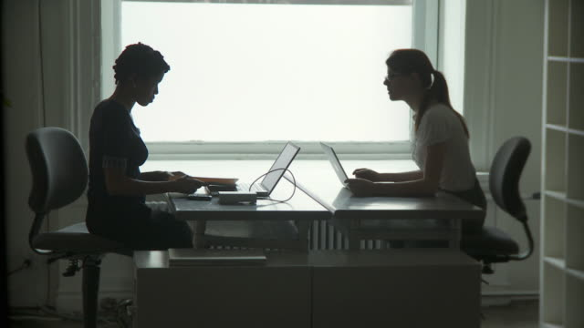 vidéos et rushes de ws silhouette of two businesswomen working on laptops and discussing files in office / new york city, new york, usa - silhouette contre jour