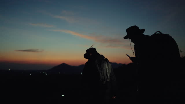 silhouette of two hiker using flashlight from smart phone during hiking. - rucksack stock videos & royalty-free footage