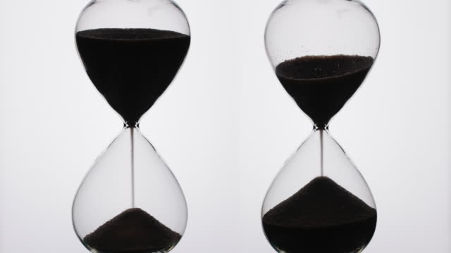 silhouette of two hour glass timers. - hourglass stock videos & royalty-free footage