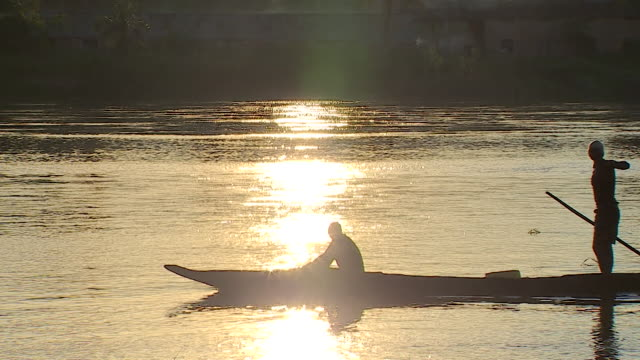 silhouette of two local african men canoeing down river in democratic republic of congo, sun shining brightly on river - democratic republic of the congo stock videos & royalty-free footage