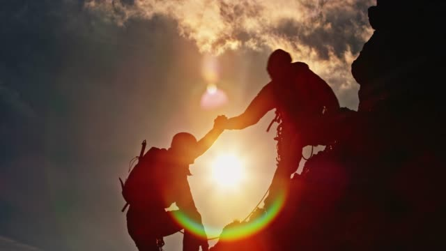 silhouette of two mountaineers climbing the top at sunset - controluce video stock e b–roll