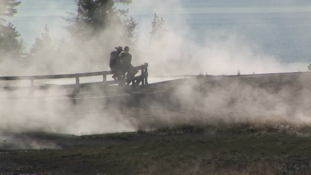 MS, Silhouette of two people sitting on fence by geysers, West Thumb Geyser Basin, Yellowstone National Park, Wyoming, USA