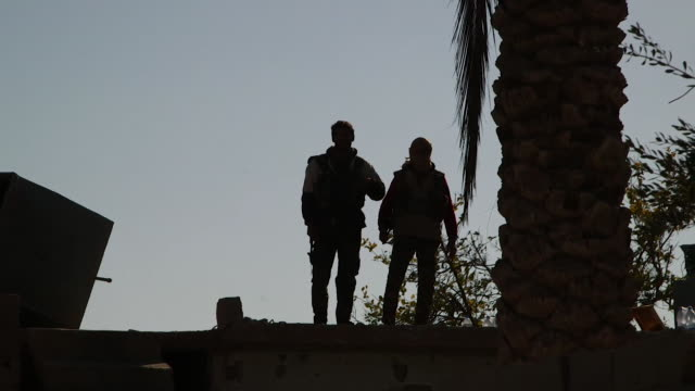 Silhouette of two Syrian Democratic Forces soldier stood on wall in Deir ezZor