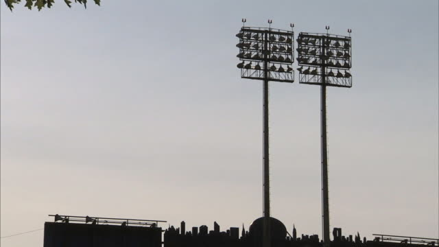 silhouette of two tall baseball park light poles above left center field food court w/ saved vintage mets shea stadium new york skyline sign below... - flushing meadows corona park stock videos and b-roll footage
