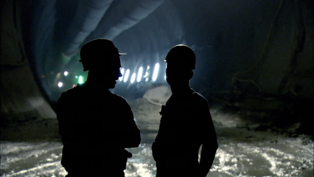 ms silhouette of two workers talking in underground tunnel construction site / amsteg, uri canton, switzerland - bergbau stock-videos und b-roll-filmmaterial