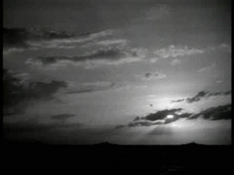 Silhouette of US battleships on the horizon at sea sun behind clouds New England coast WWII World War II US Navy