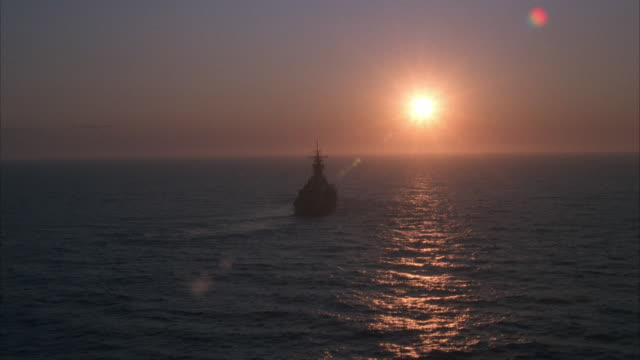 low aerial, silhouette of uss missouri on sea at sunset, aerial - uss missouri stock videos and b-roll footage