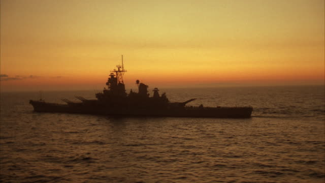LOW AERIAL, MS silhouette of USS Missouri on sea at sunset