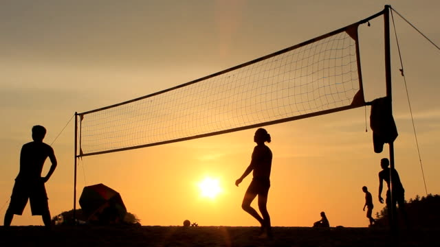 silhouette of volleyball players on the beach at sunset - volleyball sport stock videos and b-roll footage