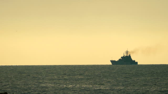 Silhouette of warship at sunset at sea