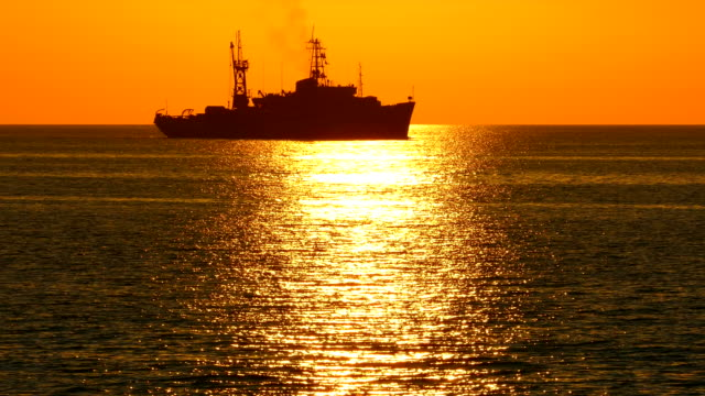 silhouette of warship at sunset - warship stock videos & royalty-free footage