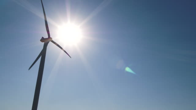 silhouette of wind turbine on sunny day - alternative energy stock videos and b-roll footage