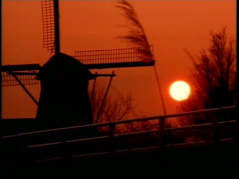 ms, silhouette of windmill against orange colored sky at sunset - unknown gender stock videos and b-roll footage