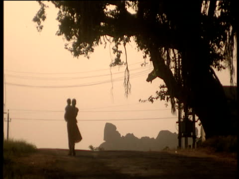 silhouette of woman carrying child on rural road india - two generation family stock videos & royalty-free footage