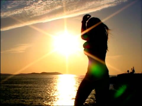 ms, silhouette of woman dancing on beach at sunset, ibiza, spain - イビサ島点の映像素材/bロール