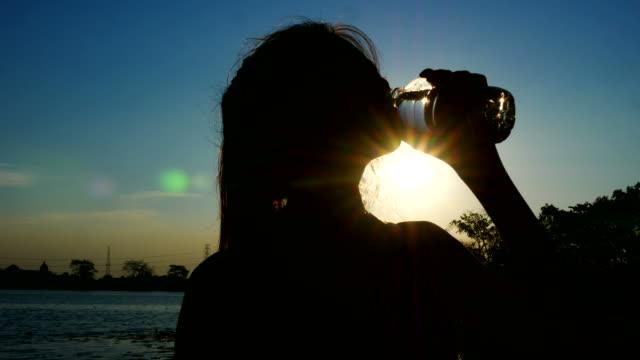 silhouette der frau trinkwasser aus flasche - wasserflasche stock-videos und b-roll-filmmaterial
