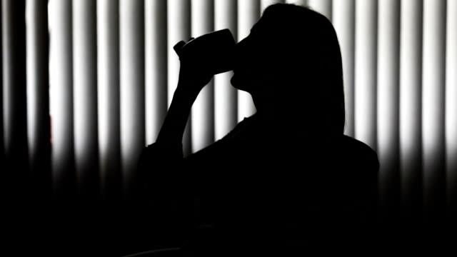 一杯のコーヒーを楽しんでいる女性のシルエット - 横顔点の映像素材/bロール