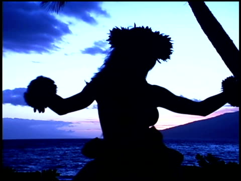 Silhouette of woman hula dancing