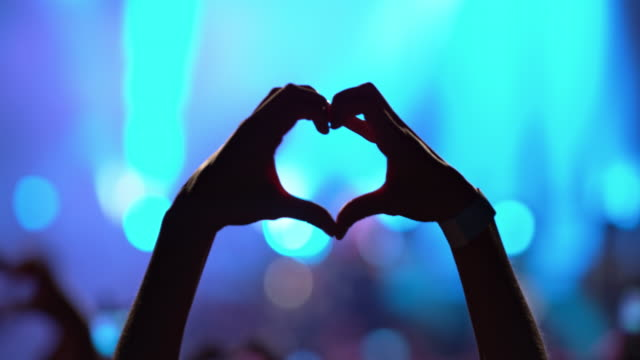 silhouette of woman making hart shape with hands at concert - コンサート点の映像素材/bロール