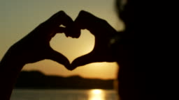 Silhouette Of Woman Making Heart Shape With Hands Against Sun