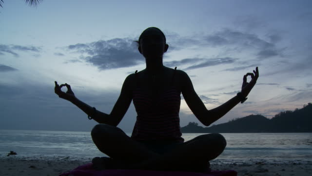 ws silhouette of woman meditating on beach at dusk / seychelles - cross legged stock videos & royalty-free footage
