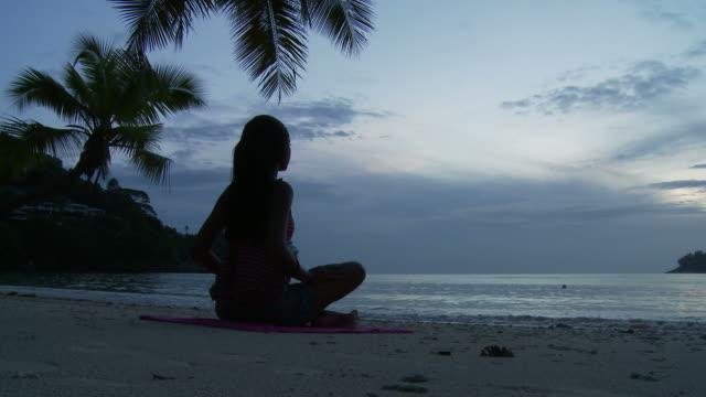 vidéos et rushes de ws silhouette of woman meditating on beach at dusk / seychelles - assis en tailleur