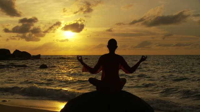 vídeos y material grabado en eventos de stock de ws silhouette of woman meditating on boulder on beach at sunset / seychelles - boulder rock