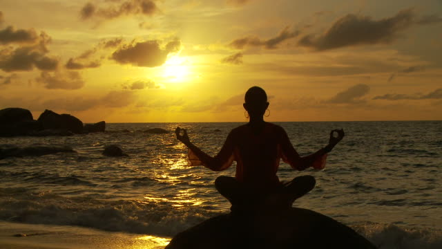 vídeos y material grabado en eventos de stock de ws silhouette of woman meditating on boulder on beach at sunset / seychelles - posición del loto