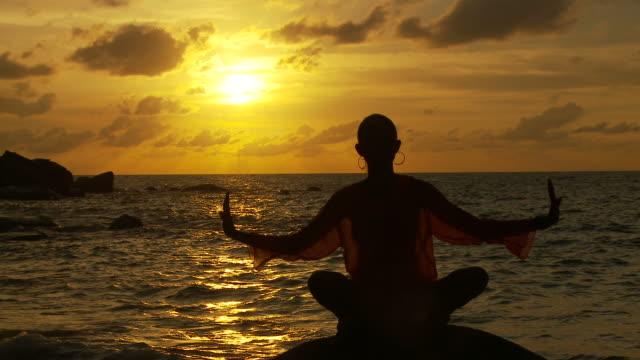 vídeos y material grabado en eventos de stock de ws silhouette of woman meditating on boulder on beach at sunset / seychelles - brazo humano