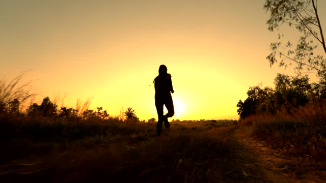 silhouette of woman running slow motion at sunset, concept exercising and healthy, slow motion - silhouette stock videos & royalty-free footage